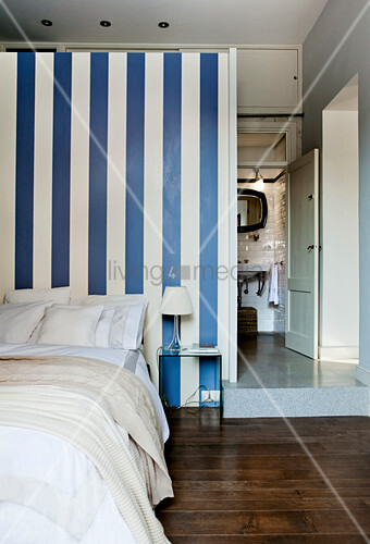Bed room with doorway leading into raised bathroom behind blue-and-white striped partition wall in small apartment