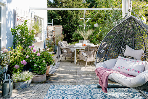 Terrace furniture, outdoor rug and hanging chair on terrace in autumn