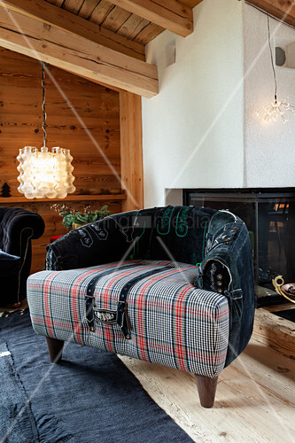 Armchair with tartan seat and embroidered leather backrest in front of fireplace
