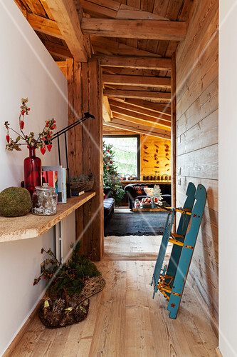 Sledge and Christmas decorations in rustic, narrow hallway