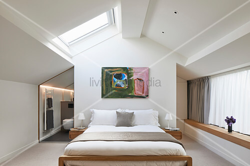 Double bed in bright bedroom with skylight and ensuite bathroom