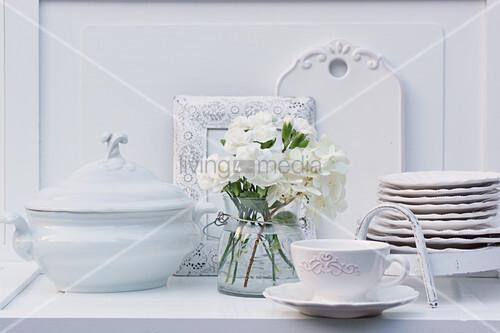 Weißer Strauß aus Nelken und Hortensienblüte und Buffet mit Porzellangeschirr
