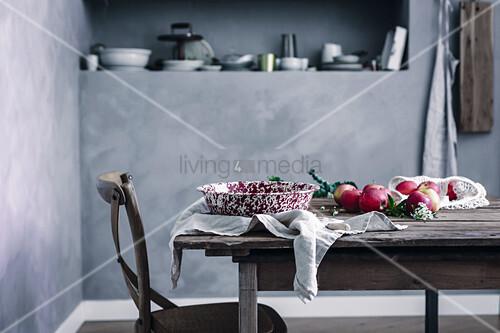 Äpfel und Vintage-Emailleschale auf Holztisch in Landhausküche