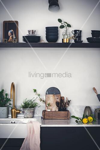 Utensilien und Deko auf Wandregal und neben Küchenspüle mit goldfarbener Armatur
