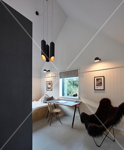 Fell-Sessel neben dem Schreibtisch im Schlafzimmer in Grautönen