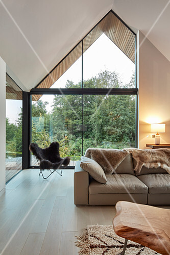 Modern living room with open roof space and glazed gable end wall