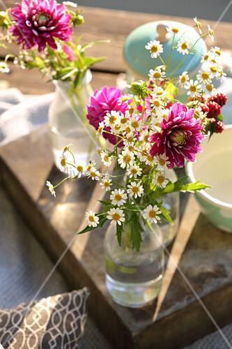 Garden flowers in glass bottles as decoration for picnic on lake