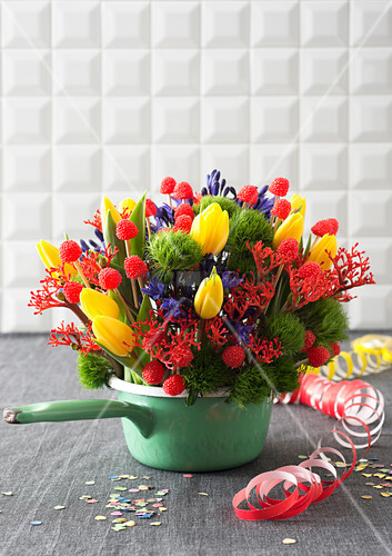 Colourful arrangement of tulips, jatropha and agapanthus in saucepan