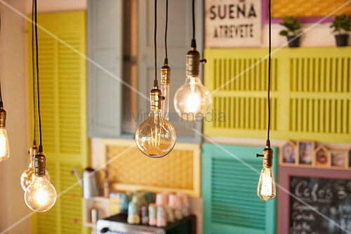 Pendant bulbs in retro style glowing against blurred wall