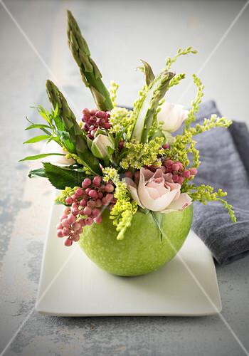 Frühlingsgesteck mit Rosen und Spargel in einem grünen Apfel