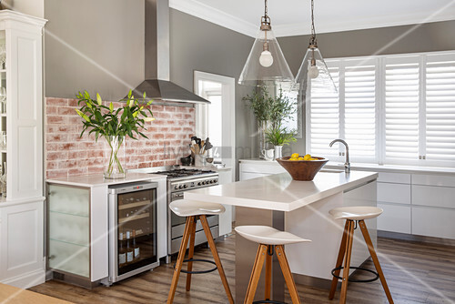 Barstools at counter in modern kitchen decorated in grey and white