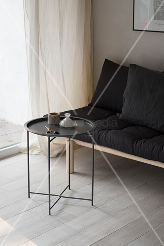 Simple futon sofa with black cushions and side table in corner