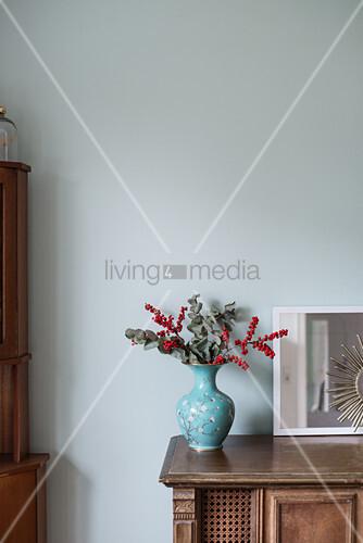 Ilex-Zweige mit roten Beeren und Eukalyptus in einer blauen Vase