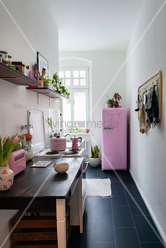 Dark tiled floor in narrow kitchen with pink fridge at far end