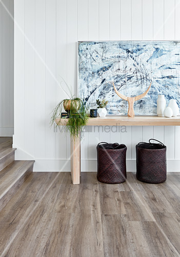 Baskets below console table and painting on board wall in hallway