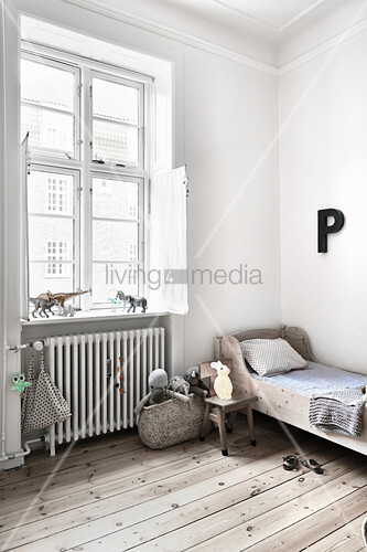 Wooden bed and letter P on white wall in child's bedroom