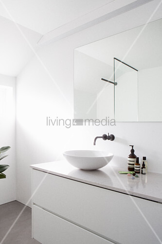 Washstand and mirror in white bathroom