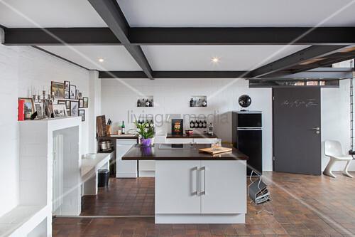 Offene Küche im Industriestil mit Kücheninsel und braunem Boden