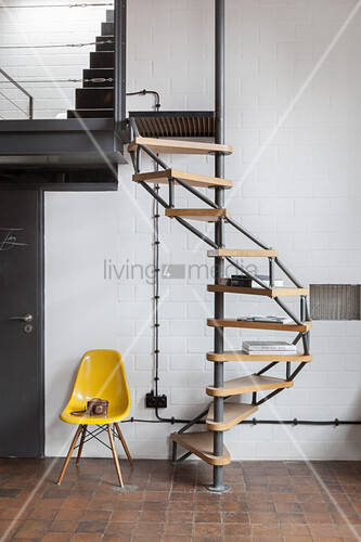 Designer chair next to spiral staircase against white wall