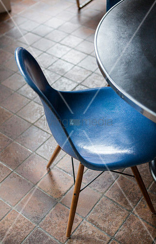 Blue designer chair at round table on brown tiled floor
