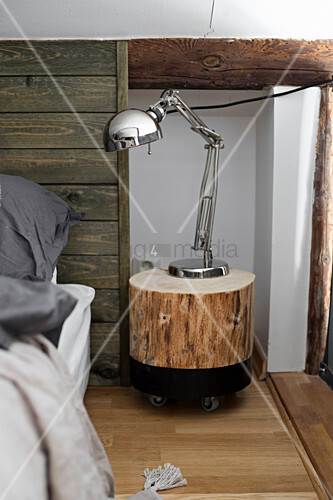 Chrome reading lamp on DIY tree-stump bedside table next to bed
