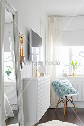 Table lamp on narrow, white, floating cabinet below wall-mounted TV and classic chair in corner below window