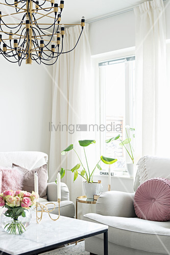 White sofa set and houseplant on side table below window; vase of roses of coffee table in foreground