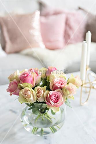 Rosenstrauß in Kugelvase und Kerzenhalter auf Couchtisch, im Hintergrund Sofa mit Dekokissen