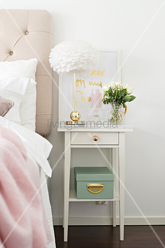Table lamp with brass base and vase of flowers on white bedside cabinet with brass drawer knob and marble top