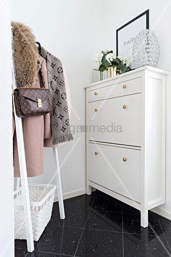 White shoe cabinet with brass knobs and coat rack in hallway