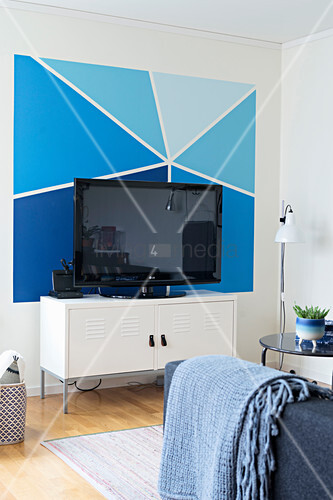 Wall painted in various shades of blue behind TV