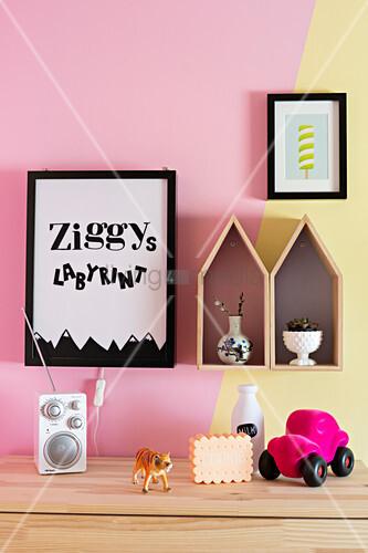 Bilder und Dekohäuser an zweifarbig gestrichener Wand im Kinderzimmer