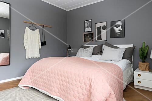 Rosa Tagesdecke über dem Bett im Schlafzimmer mit grauen Wänden