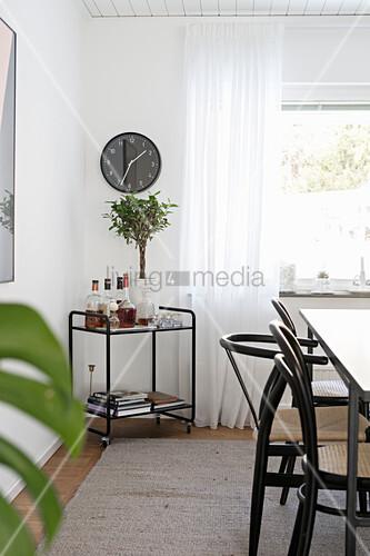 Delicate drinks trolley below wall clock in dining room