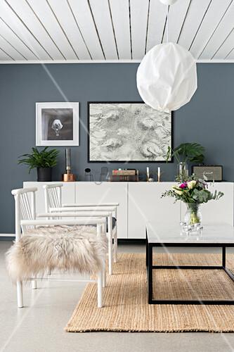 Weiße Stühle vor dem Couchtisch im Wohnzimmer mit grauen Wänden ...