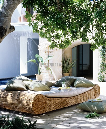 Comfortable wicker lounger with cushions in dappled shade below a tree