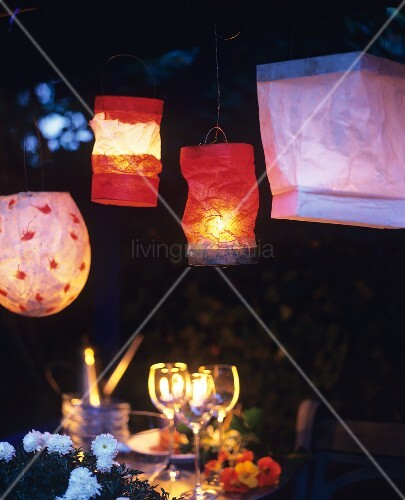 Various paper lanterns above set table in garden at twilight