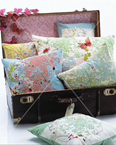 Floral cushion in old suitcase