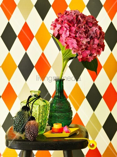 Arrangement of accessories in front of diamond-patterned wallpaper