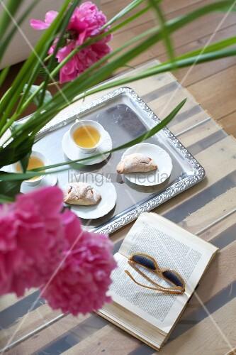 Tablett mit Gebäck und Tee neben Buch und pinkfarbenen Pfingstrosen