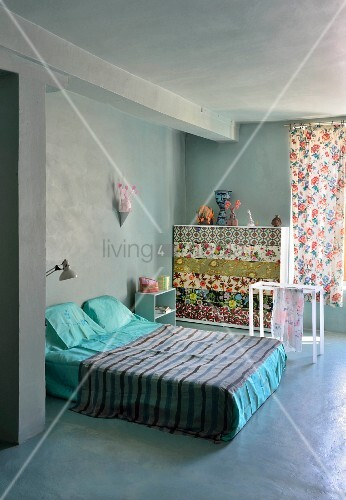 Brightly coloured accessories in grey bedroom