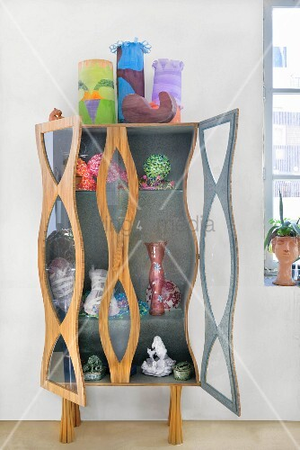 Collection of artworks on and in sculptural cabinet