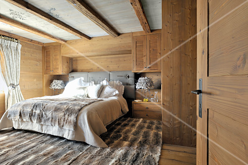 Fur rug and wood-clad walls in rustic bedroom