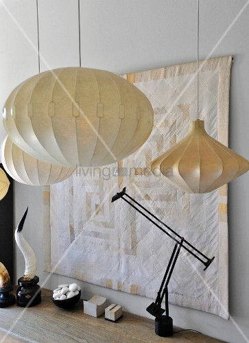 Black table lamp and various pendant lamps in front of quilted wall hanging