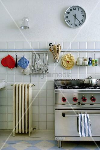 Kitchen utensils hung above gas cooker in retro kitchen