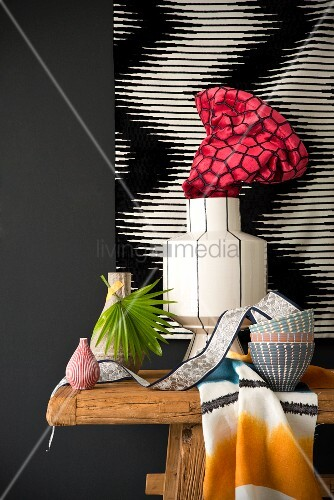 Still-life arrangement of vases and bowls on wooden table against black and white artwork on wall