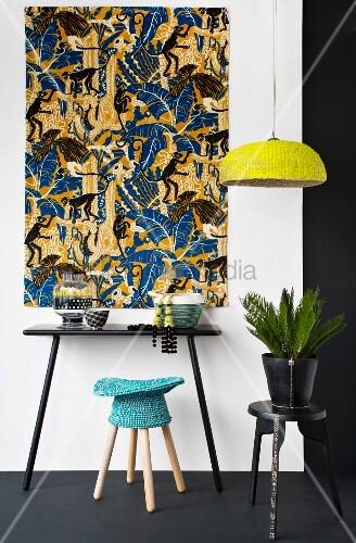 Ethno-Hocker vor Wandtisch und afrikanischem Wandbehang