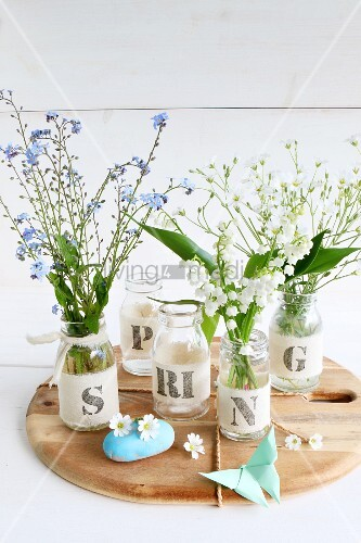 Spring flowers in jars decorated with ribbons and letters