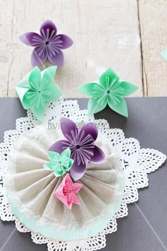 Aus Papier gebastelte Blumen auf Spitze und Stoffrosette
