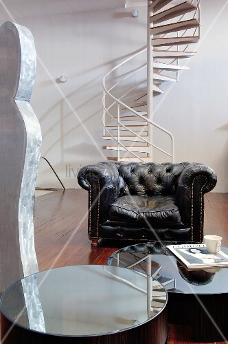 Runde Spiegeltische und ein Ledersessel vor einer Wendeltreppe